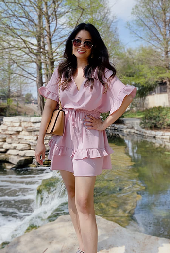 a reviewer wearing the romper in light pink