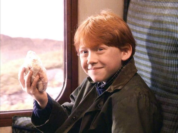 Ron holds a pre-packed snack and smiles