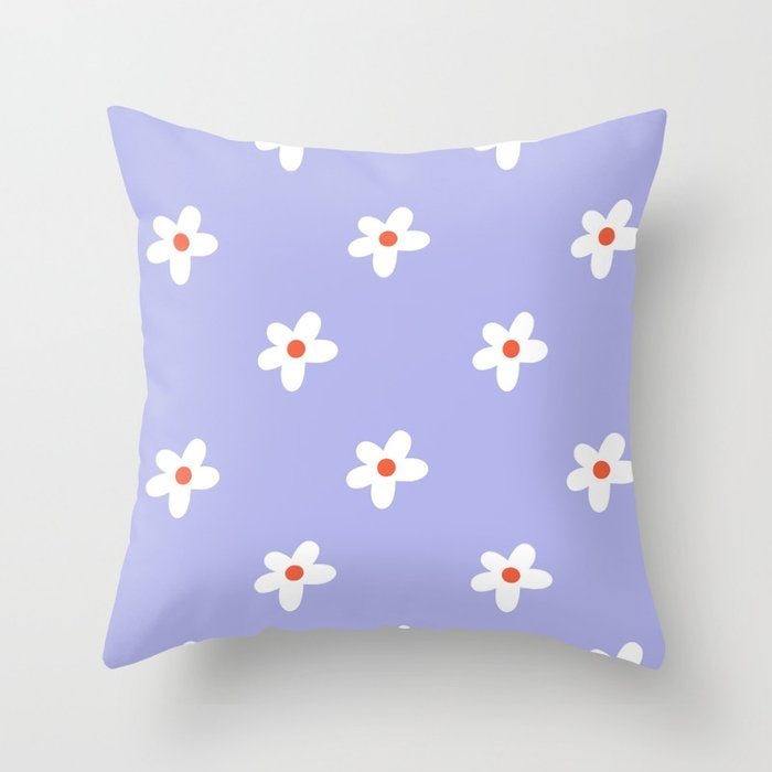 a purple throw pillow with a white floral pattern