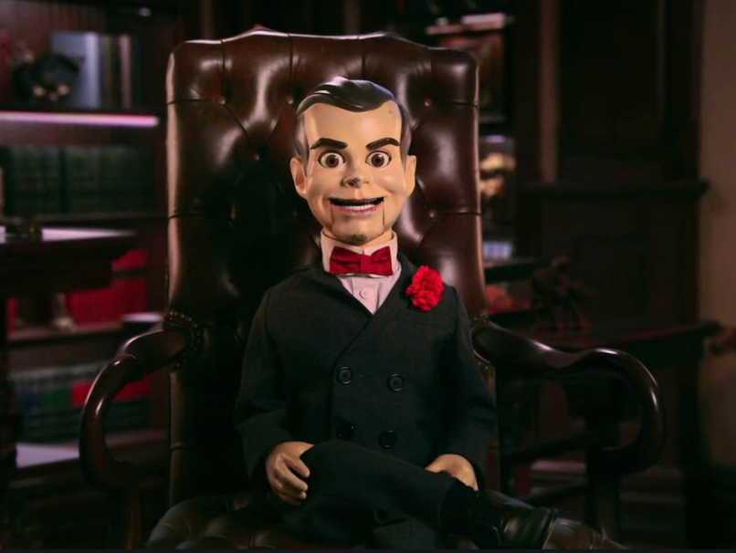 A dummy doll in a leather chair