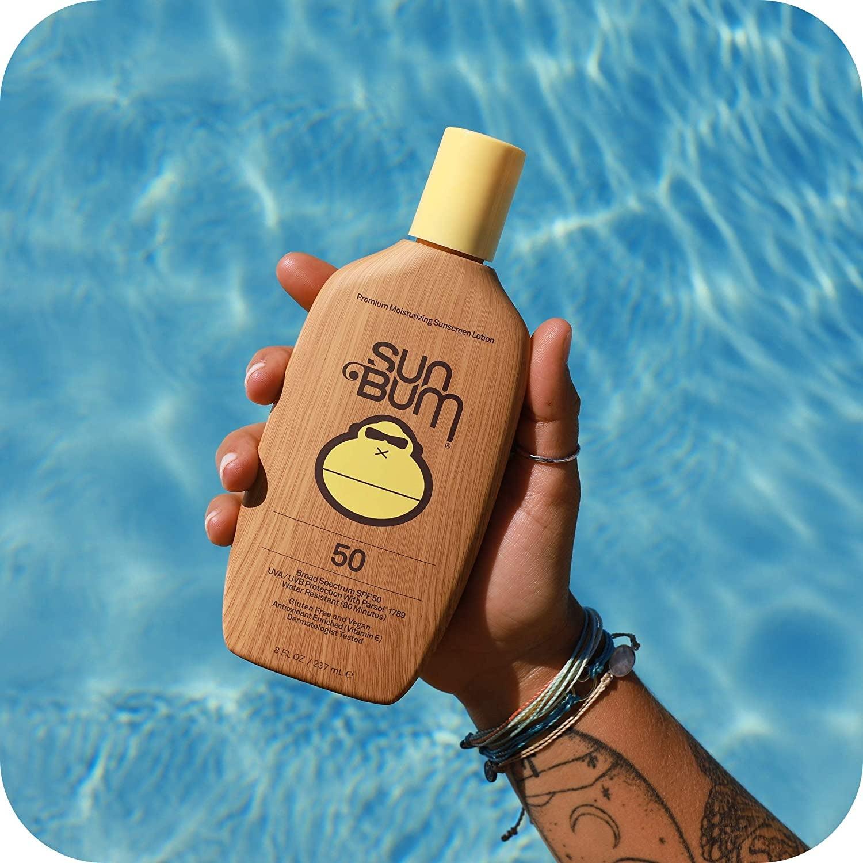 brown bottle of Sun Bum SPF 50 sunscreen in hand