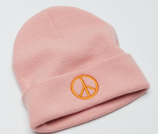 A light pink beanie with a peace sign on the front