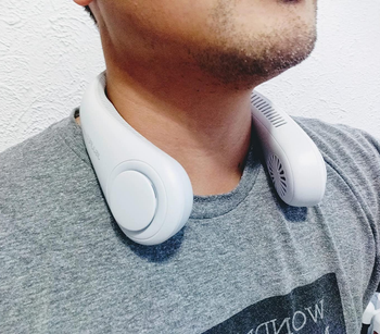 reviewer wearing the white fan around their neck
