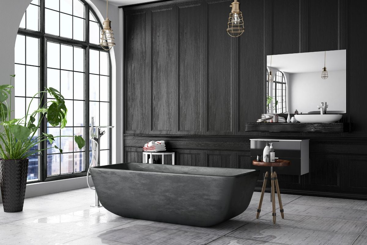 A dark bathroom with dark wood paneling, a tub in the middle of the room, and a large window to the left