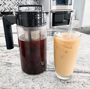 The pitcher full of cold brew next to a cup of iced coffee