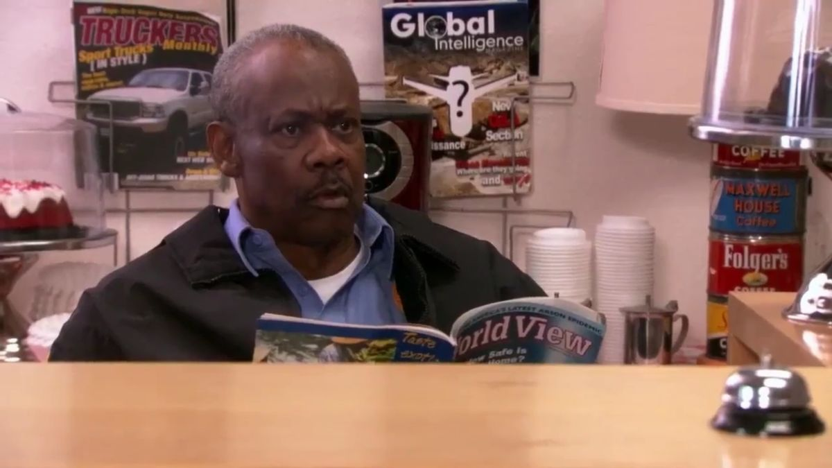 Hank Tate is sitting at the front desk, reading a magazine
