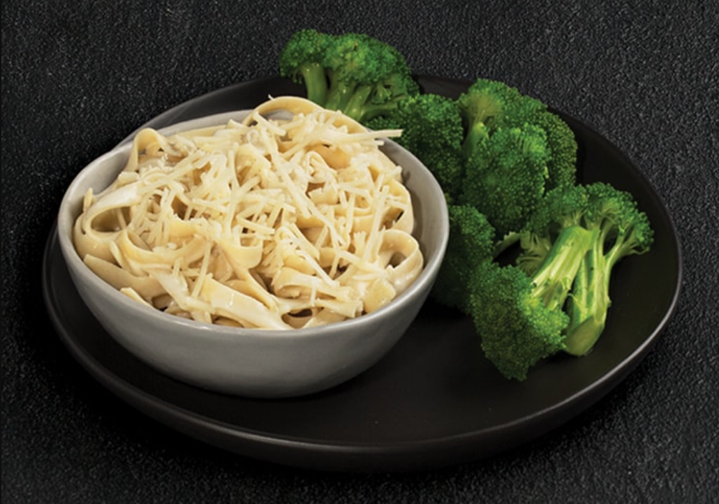 A bowl of buttered pasta with a side of broccoli