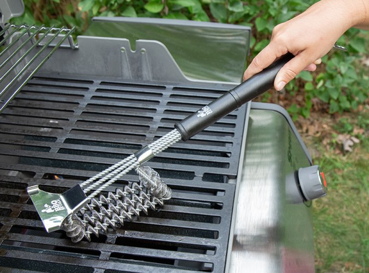 a model using the grill brush to clean an outdoor grill grate