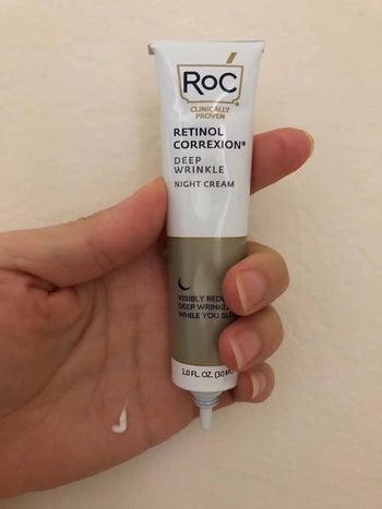Reviewer holding tube of Roc Retinol night cream