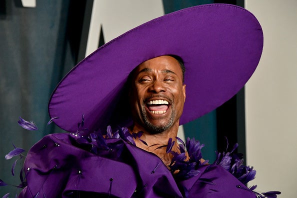 A man wears a large circular hat and a poofy dress with feathers. His mouth is open wide so you can see his teeth, and he is smiling so hard that his eyes are closed