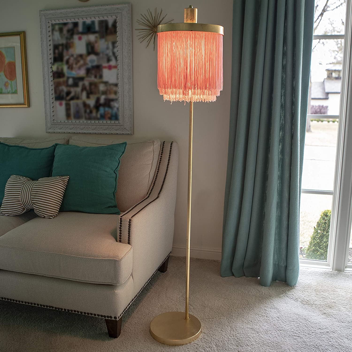 living room with gold tone floor lamp that has a pink fringe shade on it