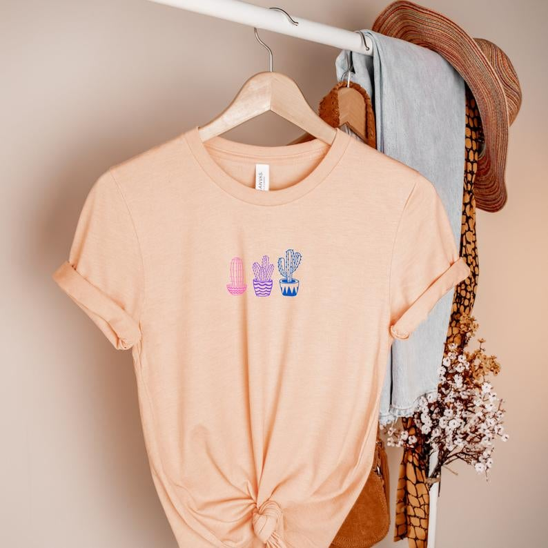 the peach tee with graphic of pink, purple, and blue cactuses