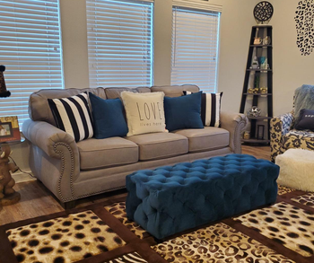 a reviewer photo of the couch with the ottoman sitting in front of it as a coffee table