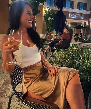 reviewer wearing gold skirt