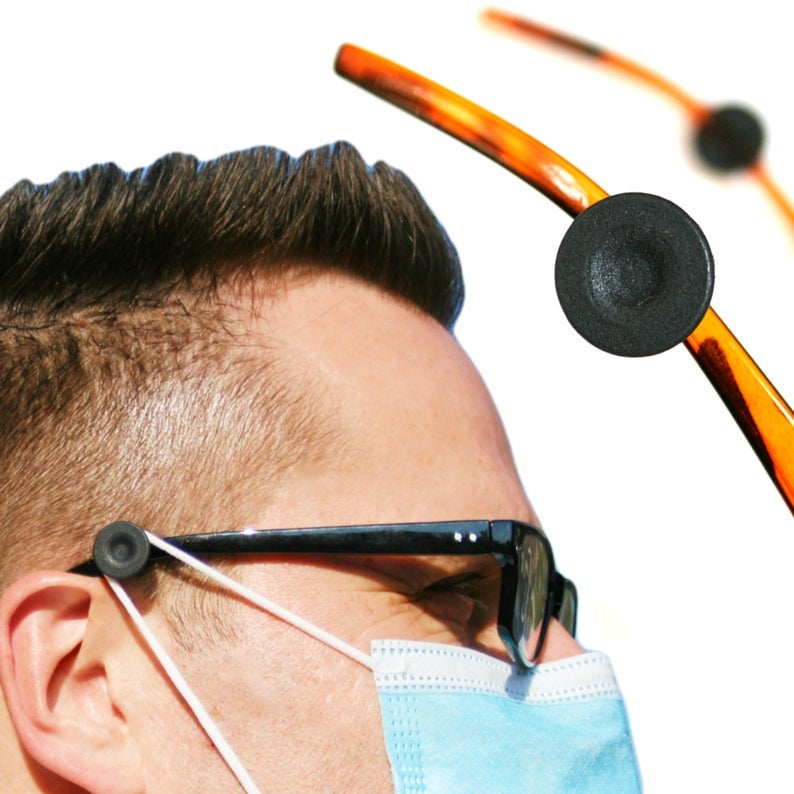 model wearing glasses with the product attached to the side, with their mask hooked around the round hook rather than their ear