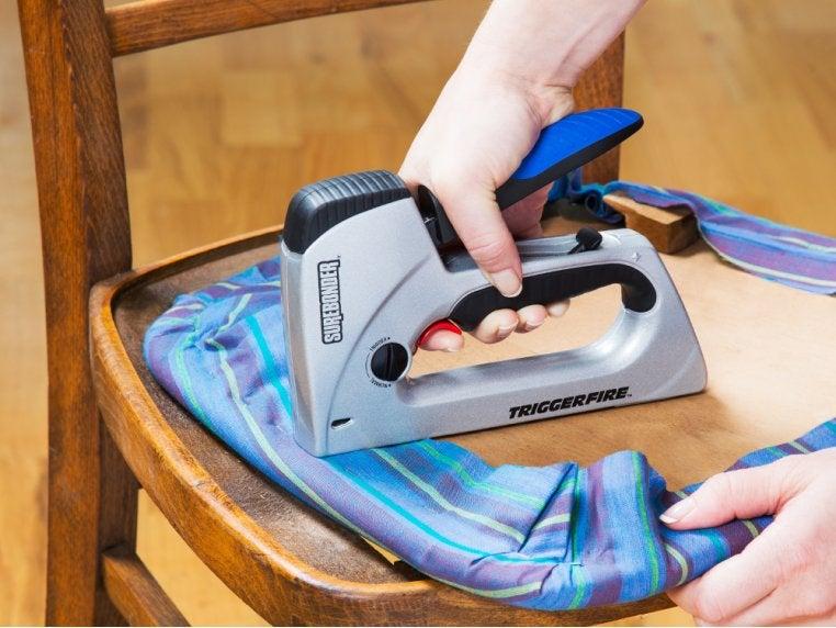 hand using the gun to staple fabric to wood