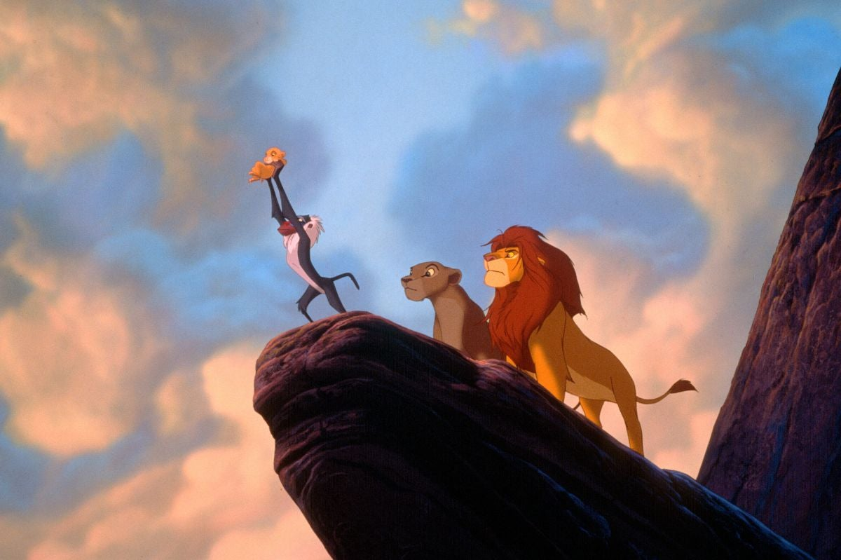 Rafiki holds Simba up in the air as Mufasa and Sarabi look on