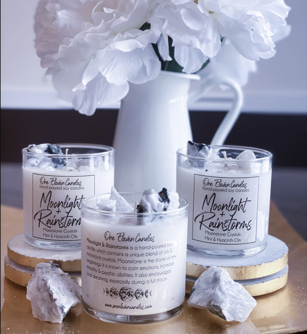 Three candles are displayed next to crystals and a vase filled with white flowers
