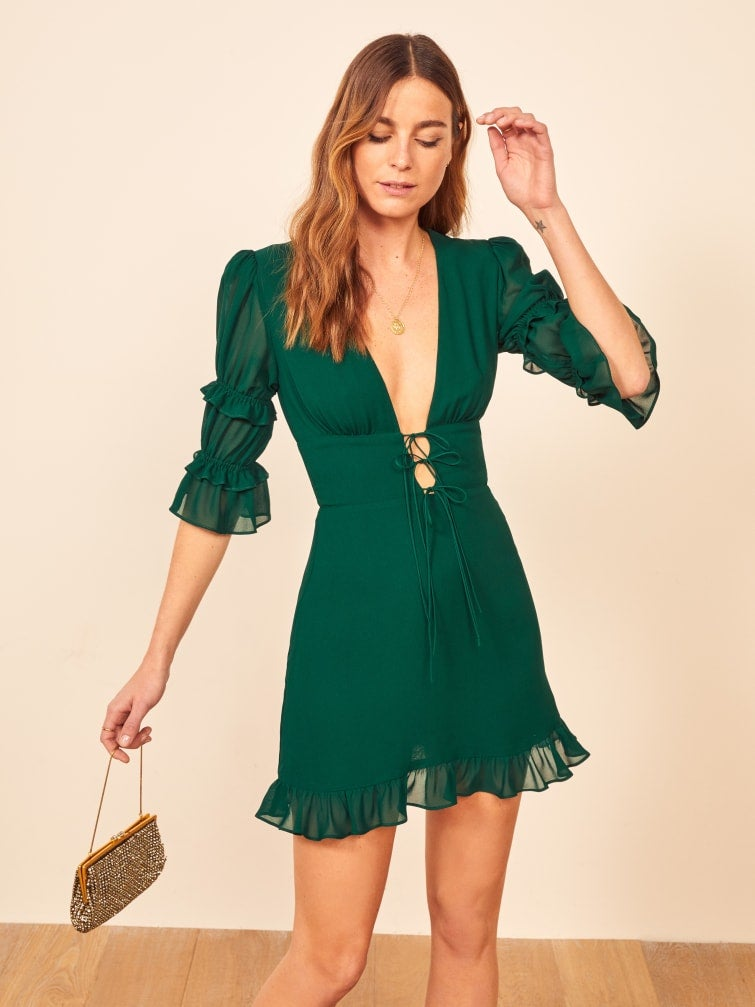 A short dress with ruched 3/4 length sleeves and a plunging neckline