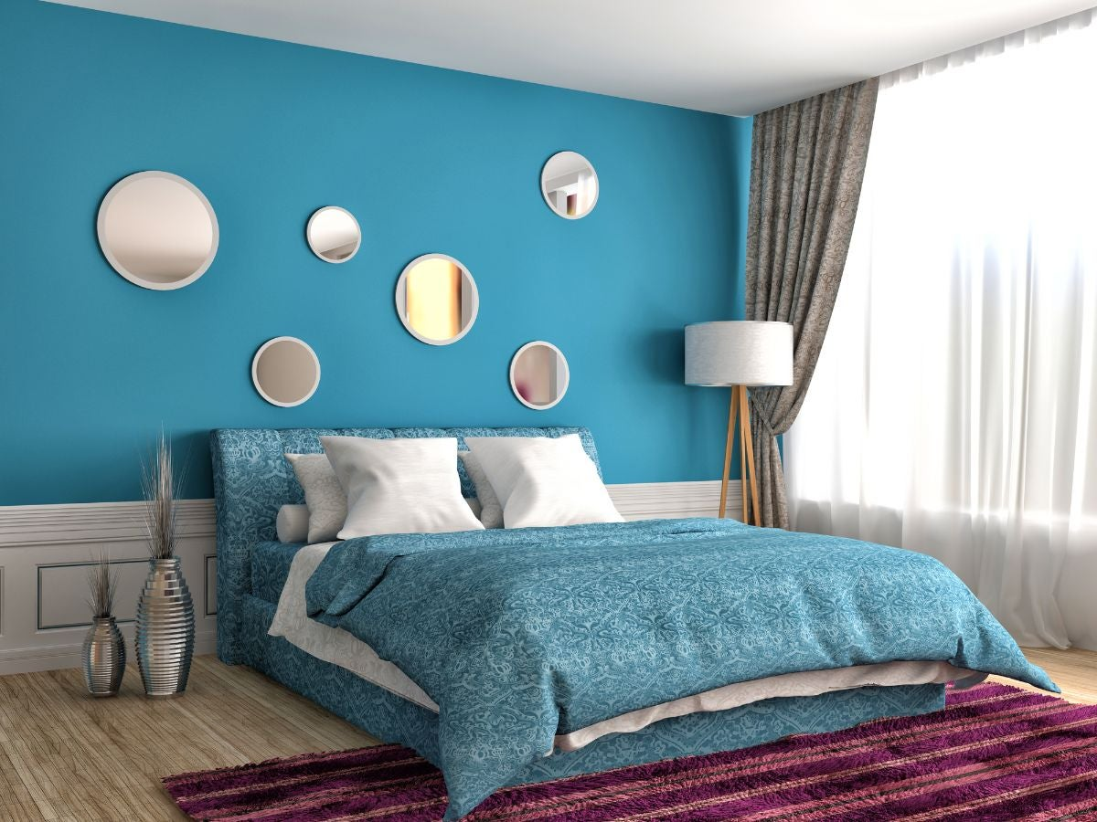 A modern bedroom with a large bed with circular mirrors hanging on the wall above it, a plush rug in front of it, and large windows to the right of it
