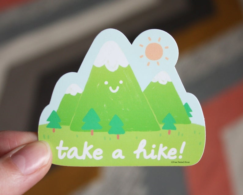 green sticker featuring a smiley mountain range and the words