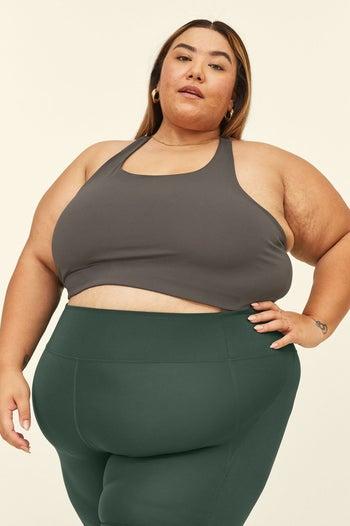 Model in the mid-length scoop neck sports bra in gray