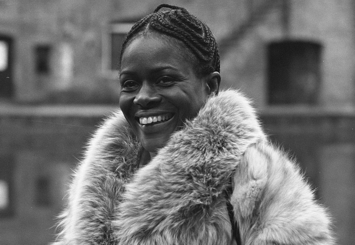 A woman with tight and detailed braids in her hair is smiling and wearing a fur coat