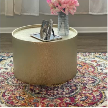 round gold table with flowers and picture frames on it in a reviewer's home