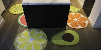 a kitchen floor covered in area rugs shaped like different foods, including an avocado