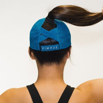 Model showing back of the hat where there's a cross hatch design to support a high ponytail
