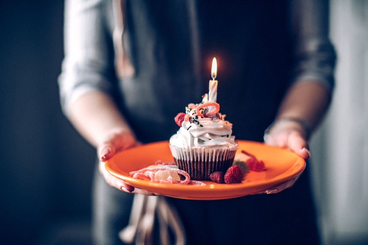 A chocolate cupcake with vanilla frosting and a candle in it