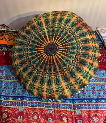 a reviewer photo of the pillow cover on a pillow sitting on a bed