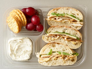 A turkey sandwich with crackers, vegetable spread, and grapes