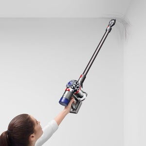 a model using the extended vacuum to clean the corner of a all