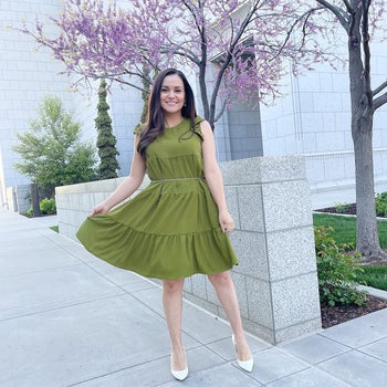 reviewer wearing the green dress with white pointed heels