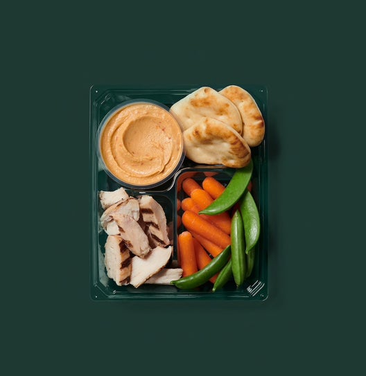 A box of grilled chicken, carrots and snap peas, naan, and a small container of hummus