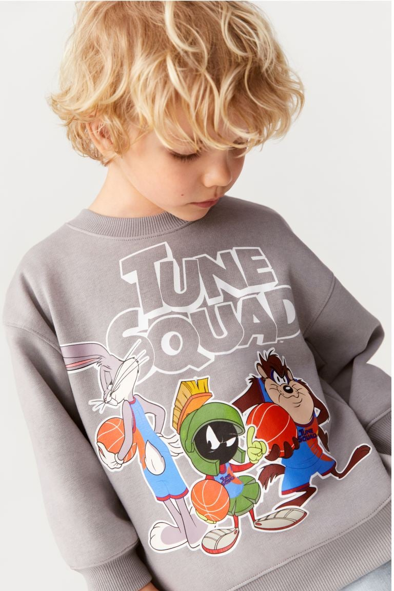 a child model in a gray sweatshirt with bugs bunny and the tune squad on it