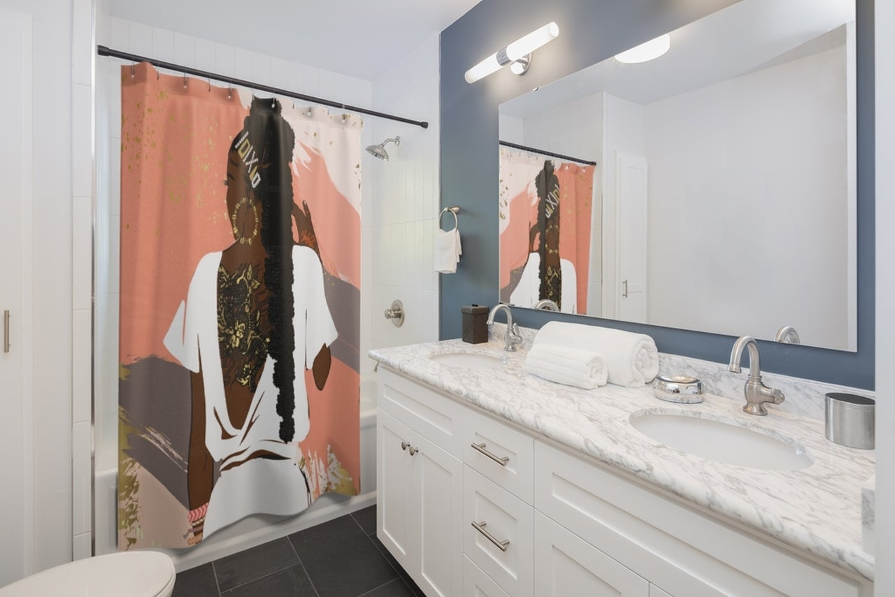 In a bathroom a shower curtain with the design of a woman from behind is shown