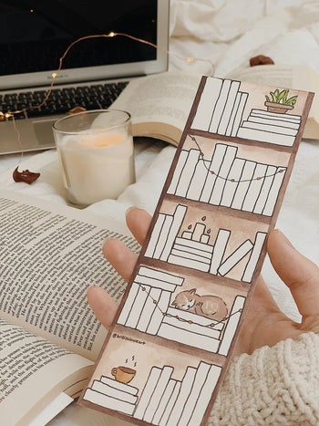 hand holding the blank bookmark illustrated with books on shelves with plants and a cat