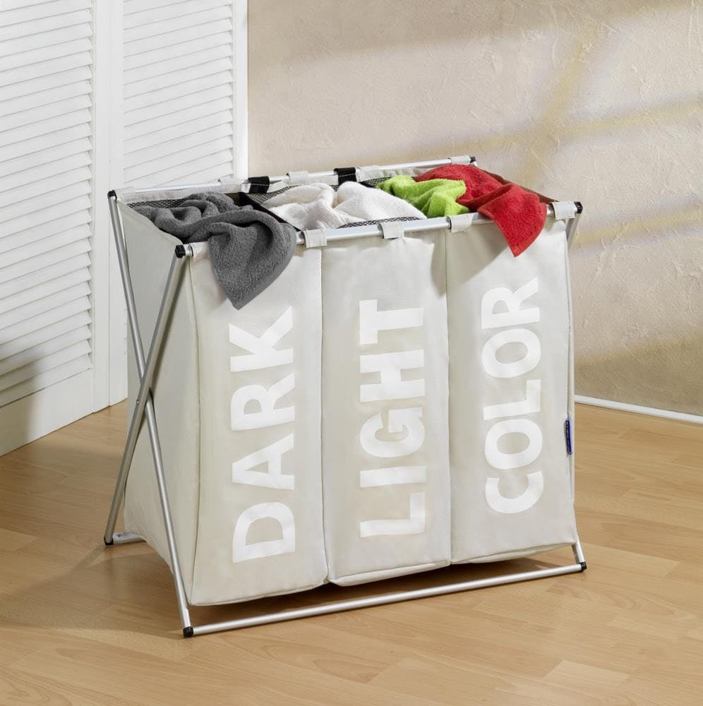 The cream colored three-section hamper that says dark light and color