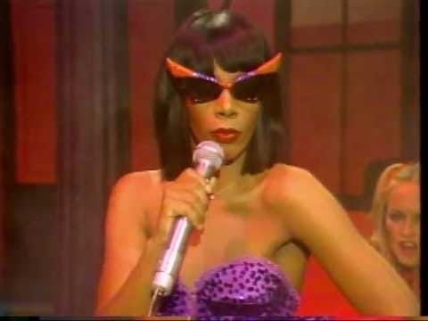 A woman wears sunglasses that point on top toward the sky. She holds a microphone and wears a rhinestone dress