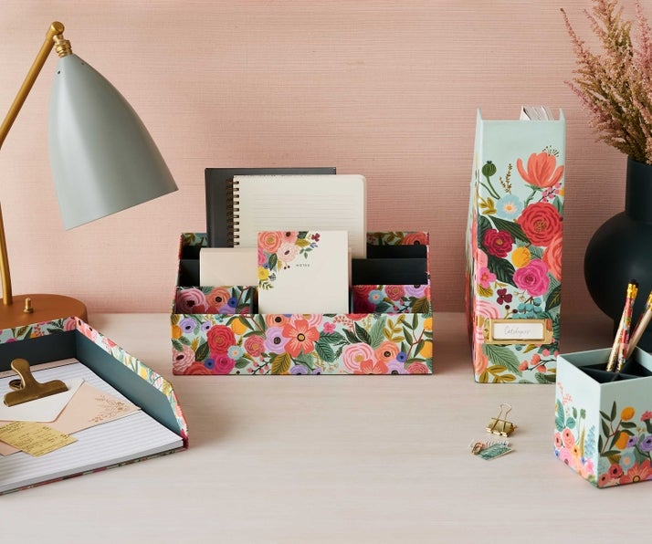 the organizer with three small front compartments and two larger compartments on a desk holding notepads
