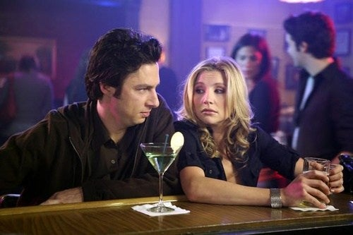a man and woman sit at a bar drinking alcohol