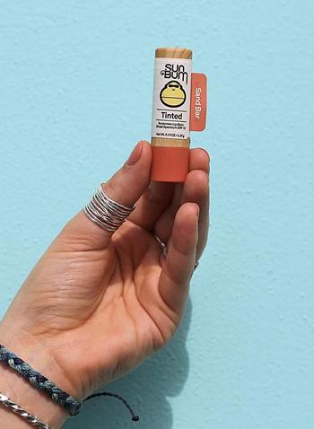 model holding tube of sunbum tinted lip balm