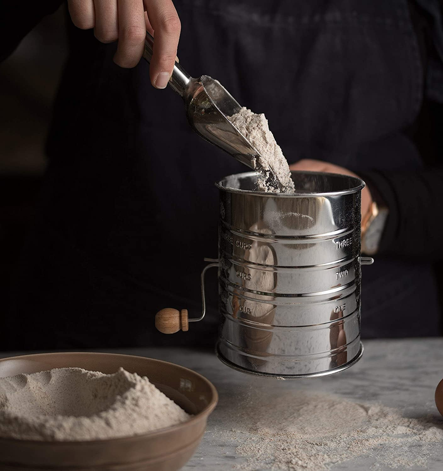 a model scooping flour into the flour sifter