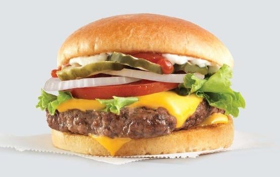 A cheeseburger with lettuce, tomato, onions, pickles, ketchup, and mayo