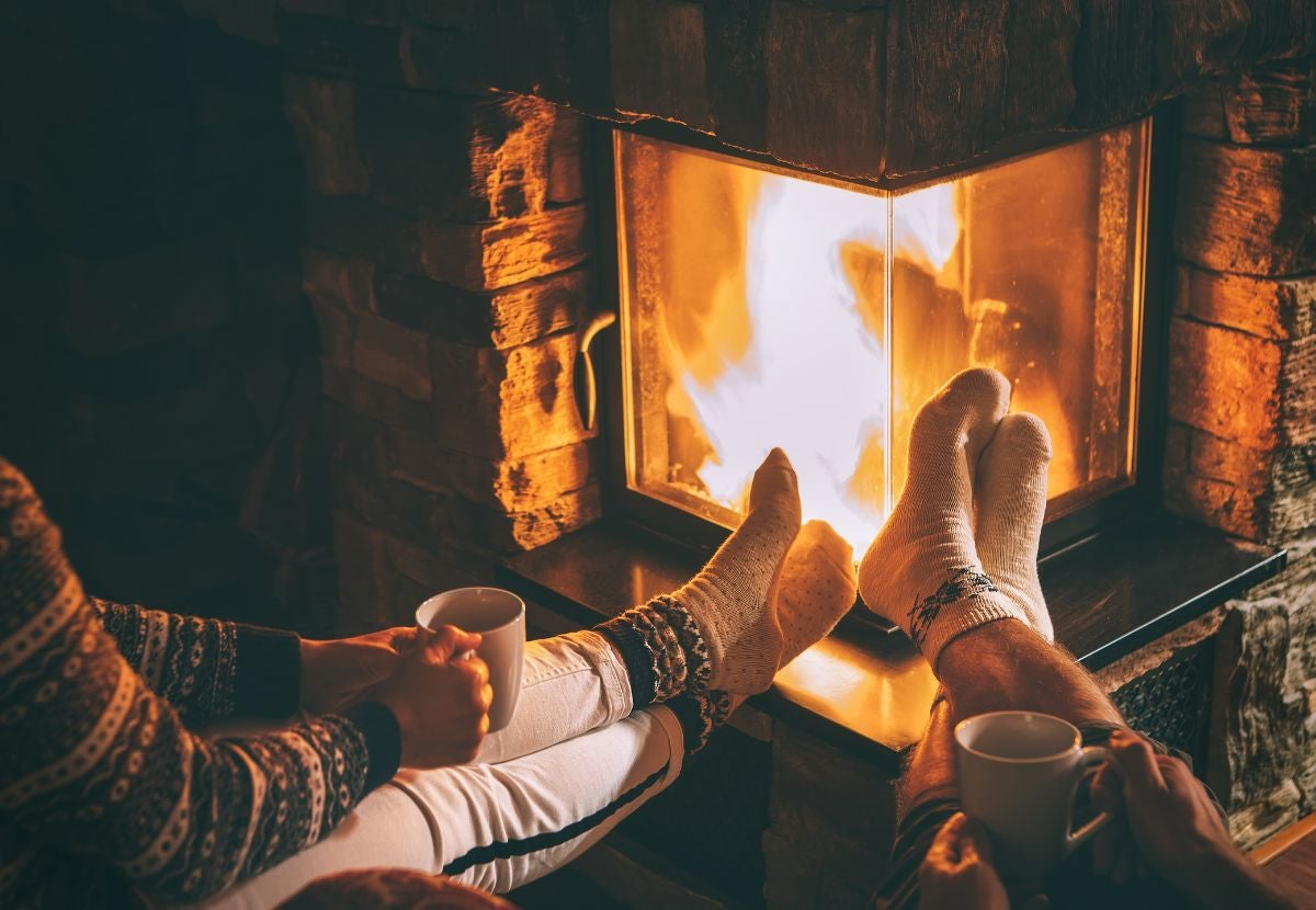 Two people hold mugs and put their sock feet next to a fireplace