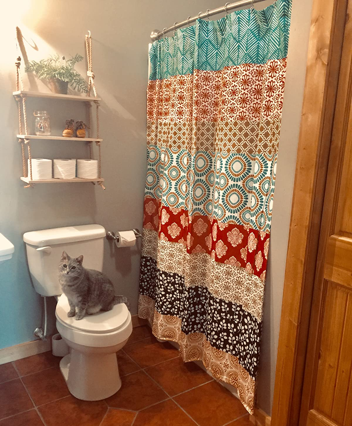 a reviewer photo of a bathroom with the shower curtain hung up and a cat sitting on a toilet