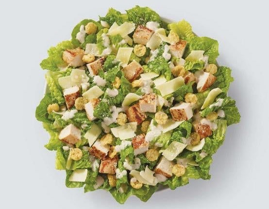 A salad with grilled chicken, cheese, Parmesan cheese crisps, and Caesar dressing