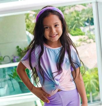 a child model wearing a purple and pink headband